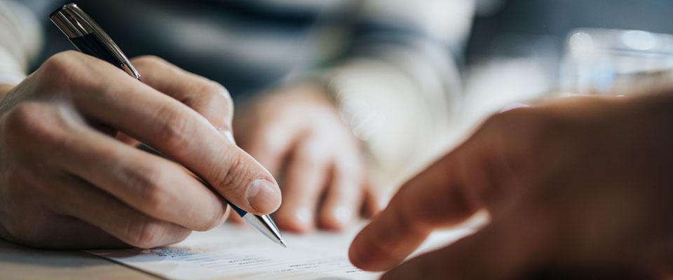 długopis trzymany wdłoni przed kartką
